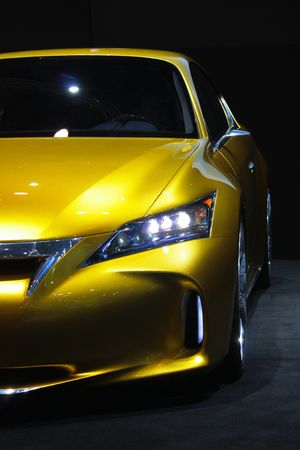 This is a yellow sports car against a dark background and with reflection.