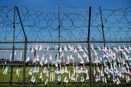 Foto de Fence with barbed wire and south korean flags at the demilitarised zone DMZ at the freedom bridge with blue sky, South Korea, Asia - Imagen libre de derechos