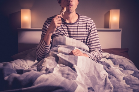 Photo for Young man eating chicken in bed - Royalty Free Image