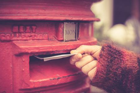 Foto de Closeup on a woman's hand as she is posting a letter - Imagen libre de derechos