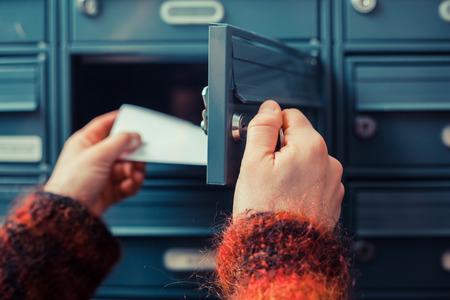 Foto de Closeup on a woman's hand as she is getting her post out of her letterbox - Imagen libre de derechos
