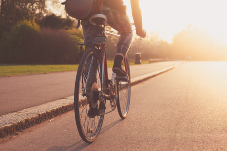 Photo for A young woman cycling into the sunset in the park - Royalty Free Image