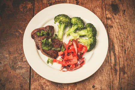 Photo for Meat and vegetables including broccoli and red peppers on a plate - Royalty Free Image