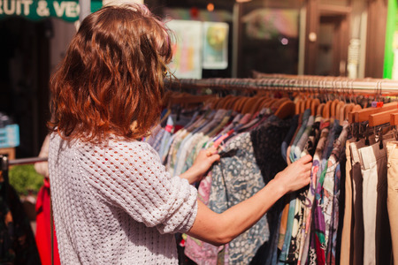 Photo for A young woman is browsing a rail of clothes at a street market - Royalty Free Image