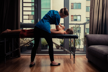 Photo pour A massage therapist is treating a female client on a table in an apartment - image libre de droit