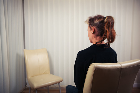 Foto de A woman is sitting on a chair and is waiting to see her doctor or therapist - Imagen libre de derechos