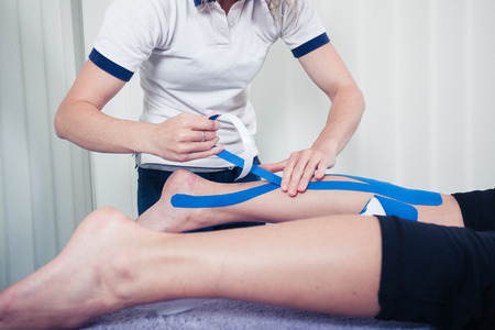 Photo pour A physiotherapist is applying kinesio tape to a patient's leg - image libre de droit
