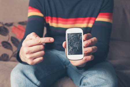 Foto de A young man is sitting on a sofa and is pointing at a broken smart phone with a cracked screen - Imagen libre de derechos