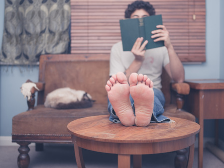 Photo pour A barefoot young man is resting his legs on a coffee table at home while reading, there is a cat on the sofa next to him - image libre de droit