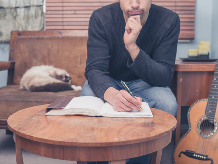 Photo pour A young man is sitting with his cat and guitar at home on a sofa and is writing songs in a notebook - image libre de droit