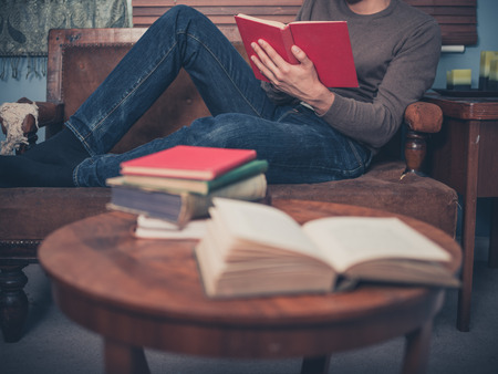 Photo pour A young man is relaxing on a sofa at home and is reading a book - image libre de droit