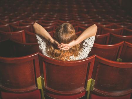 Foto de Rear view shot of a young woman sitting alone in an auditorium - Imagen libre de derechos