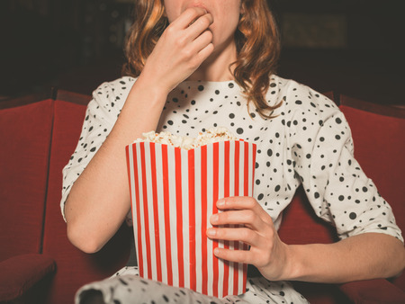 Photo pour A young woman is watching a movie and is eating popcorn at the cinema - image libre de droit