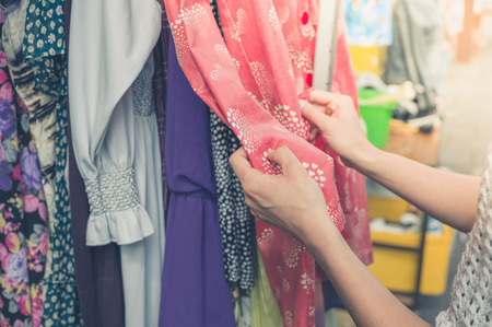 Photo for A young woman is browsing through clothing at a street market - Royalty Free Image