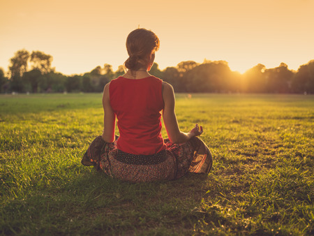 Photo pour A young woman is sitting on the grass in a park and is meditating at sunset - image libre de droit