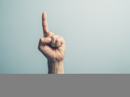 Photo for A male hand with the index finger pointing up - Royalty Free Image