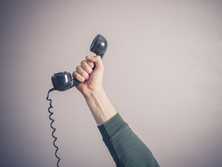 Photo pour The hand of a young man is holding a vintage rotary telephone - image libre de droit