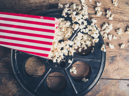 Photo for Cinema concept of vintage film reel with popcorn on wooden surface - Royalty Free Image