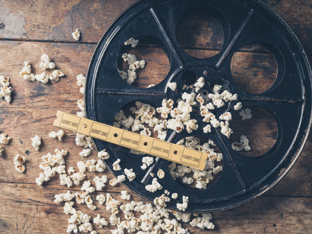 Photo for Cinema concept of vintage film reel with popcorn and movie tickets - Royalty Free Image