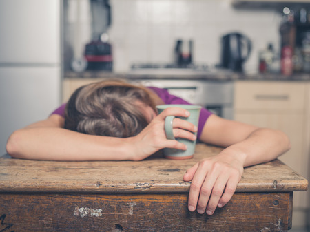 Photo pour A tired young woman is having a cup of tea and is resting her head on a table - image libre de droit
