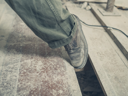 Photo pour The foot of a person tripping on a gap between the floor boards in a room undergoing renovations - image libre de droit