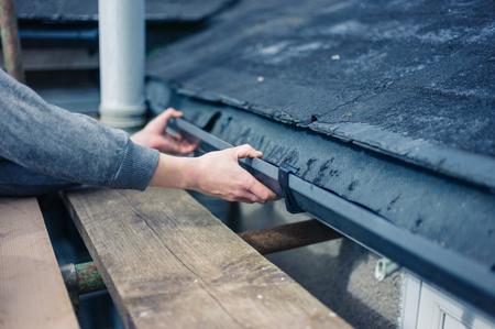 Foto de The hands of a worker fixing a drain from a scaffold - Imagen libre de derechos