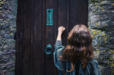 Photo for A young woman is knocking on an old wooden door - Royalty Free Image