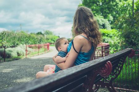 Foto de A young mother is breastfeeding her baby on a park bench - Imagen libre de derechos