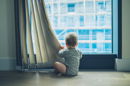 Photo pour A little baby is playing with the curtain in a high rise apartment - image libre de droit
