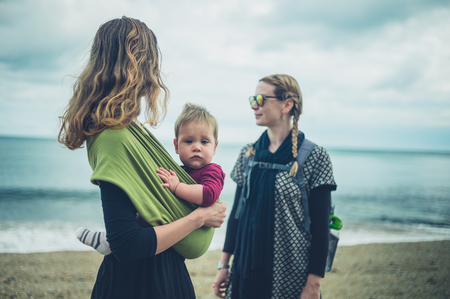 Photo for Two young women with a small baby are standing on the beach - Royalty Free Image
