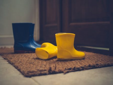 Photo for Two pairs of rubber boots by an open door - Royalty Free Image