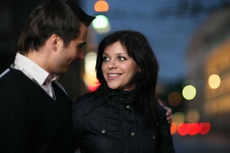 Beautiful young couple walking together in night city. Shallow DOF.