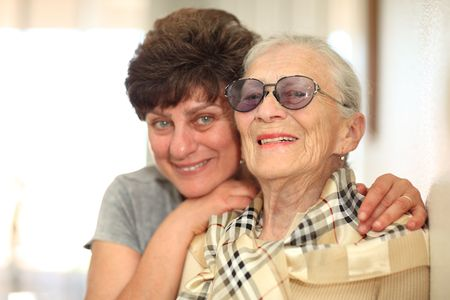 Happy woman with elderly mother, laughing together. Shallow DOF, focus on the senior woman.