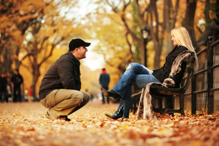Man talking to hot blond woman in autumn park. Shallow DOF.