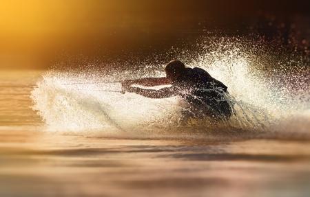 Foto de Waterskier silhouette moving fast in splashes of water at sunset - Imagen libre de derechos