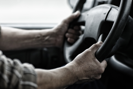 Male driver hands holding steering wheel.