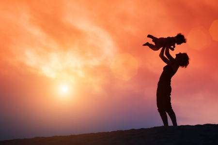 Photo pour Mother lifting toddler child in air over scenic sunset sky - image libre de droit