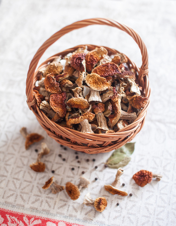 Dried white mushrooms in a beautiful wicker basket on the table