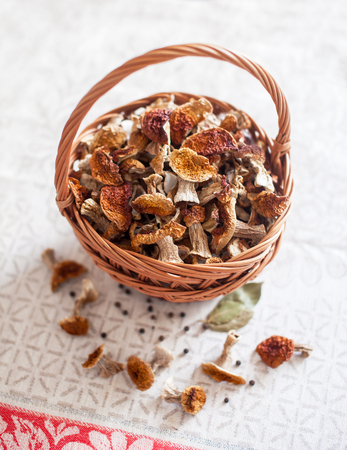 Dried white mushrooms in a beautiful wicker basket on the table.