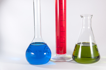 Picture showing some chemistry lab glassware: from left to right in volumetric flask with blue liquid, a graduated cylinder with a magenta liquid, an Erlenmeyer flask with a green liquid.