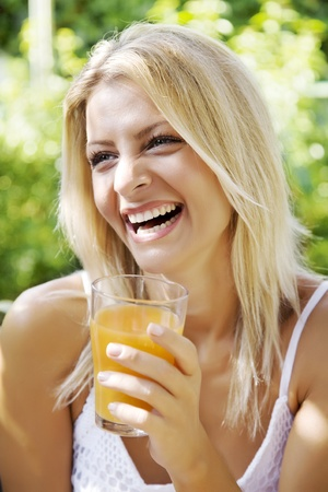 Photo for happy woman drinking her morning orange juice in her garden - Royalty Free Image