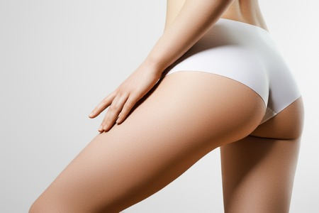 Photo pour Healthy lifestyle diet and fitness. Beautiful slim woman's body. Perfect slim toned young body of the girl. Fitness or plastic surgery and aesthetic cosmetology. Taut elastic ass. Firm buttocks - image libre de droit