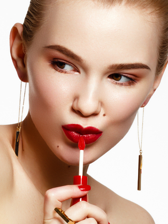 Foto de Makeup products. Young beautiful girl with gold earrings and ring smiling on white background. Red nails with manicure. A young woman with fashion accessories applying lip gloss - Imagen libre de derechos