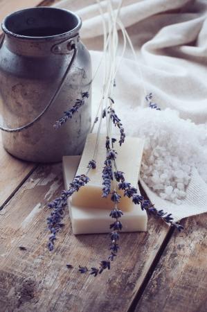 Foto de Natural soap, lavender, salt and old can on wooden board, rustic still life, hygiene items for bath and spa  - Imagen libre de derechos