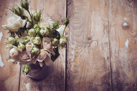Foto de Bouquet of roses in metal pot on the wooden background, vintage style - Imagen libre de derechos