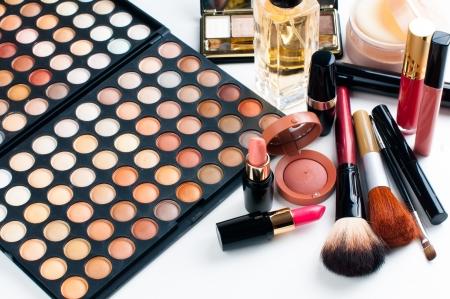 Photo pour Professional makeup set: eyeshadow palette, lipstick, mascara, blush, powder, make-up brushes and perfume, many cosmetics closeup. - image libre de droit