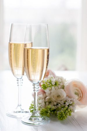 Foto de Two glasses of champagne and a beautiful tender festive wedding bouquet of flowers, buttercups and white lilac on a white painted wooden board. - Imagen libre de derechos