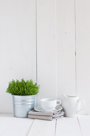Photo pour Cottage life, country kitchen decoration: a house plant in a metal pot, kitchen pottery, utensils and napkins on white painted board. Cozy home country life background is. - image libre de droit