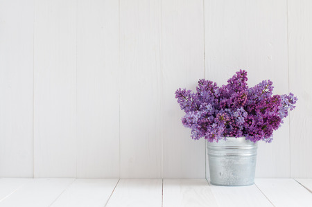 Photo pour Bouquet of beautiful spring flowers of lilac in a vase on a white vintage wooden board, home decor in a rustic style - image libre de droit