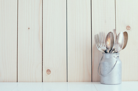 Photo for Home Kitchen Decor: vintage cutlery, spoons and forks in zinc can on a wooden board background , cozy arrangement retro style, soft pastel colors. - Royalty Free Image